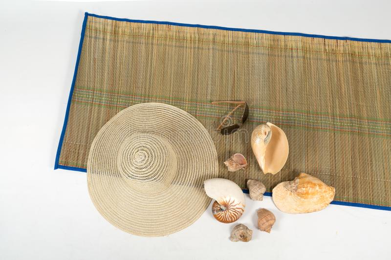 The hat, sunglasses and shells on a colorful rug on white background isolated royalty free stock images