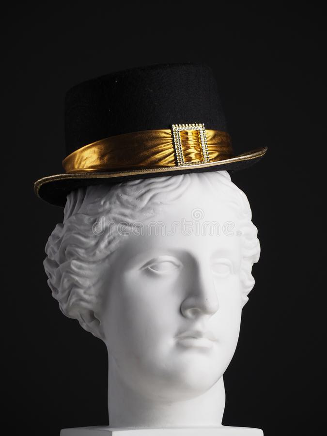 Hat always looks good on you. A black hat with a gold stripe is put on the head of Venus. The background is utterly black royalty free stock images