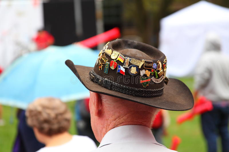 Hat with medals on head of man. Back shot of an elderly gentleman at an event in Australia, wearing a brown hat stuck with medals stock image