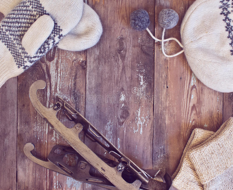 Hat, mittens and vintage skates on a wooden background. stock image