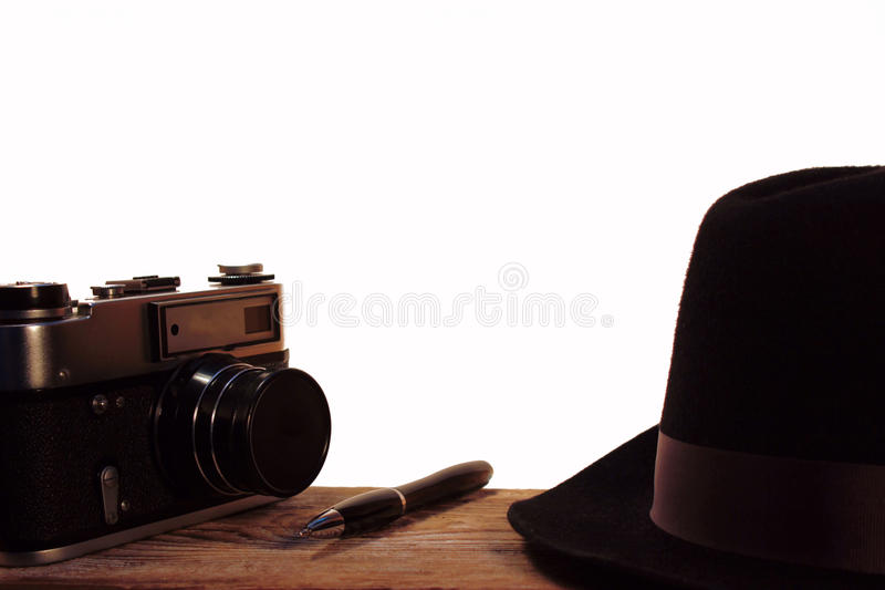 The hat and retro photo camera on white background. The Journey road accesories.Ball point pen ,wooden table stock photography