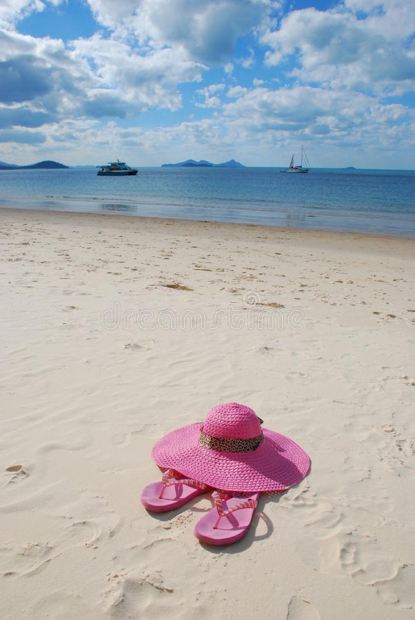 A hat and sandals on the beach stock image