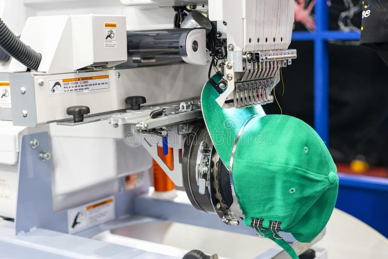 Hat sewing at modern and automatic high technology embroidery machine for textile - clothing apparel making manufacturing process. In industrial stock photo