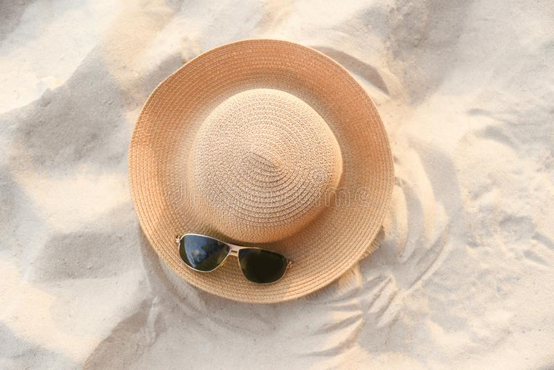 Hat summer - straw hat fasion and sunglasses accessories on sandy beach sea background top view. Hat summer / straw hat fasion and sunglasses accessories on stock photography