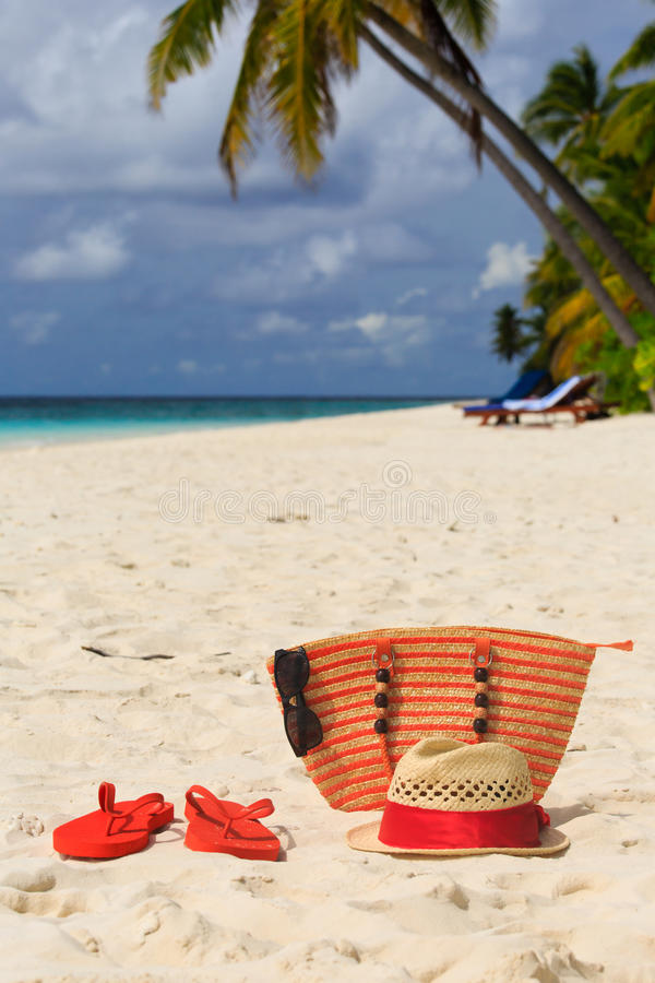 Hat, sun glasses and flip flops on a tropical beach royalty free stock photos