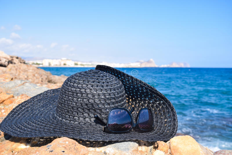Hat and sunglasses on the beach rocks royalty free stock photos