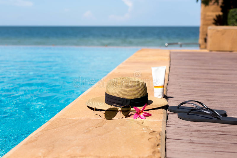 Hat, sunglasses and flip flops next to swimming pool. With beach backgroun stock photography