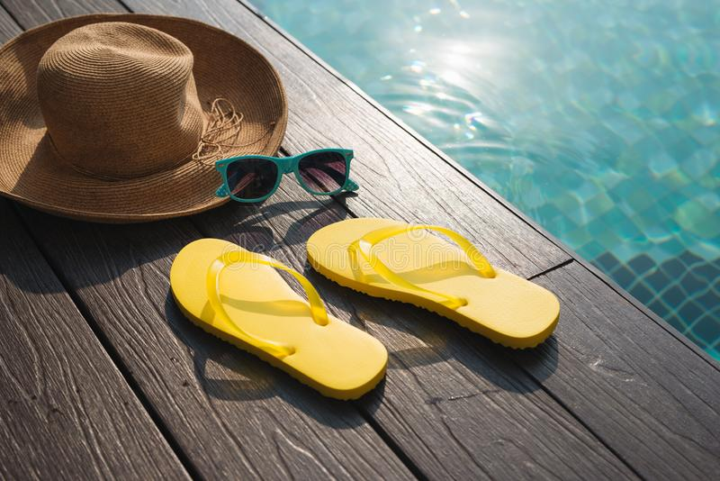 Hat, sunglasses and flip flops by swimming pool stock photo