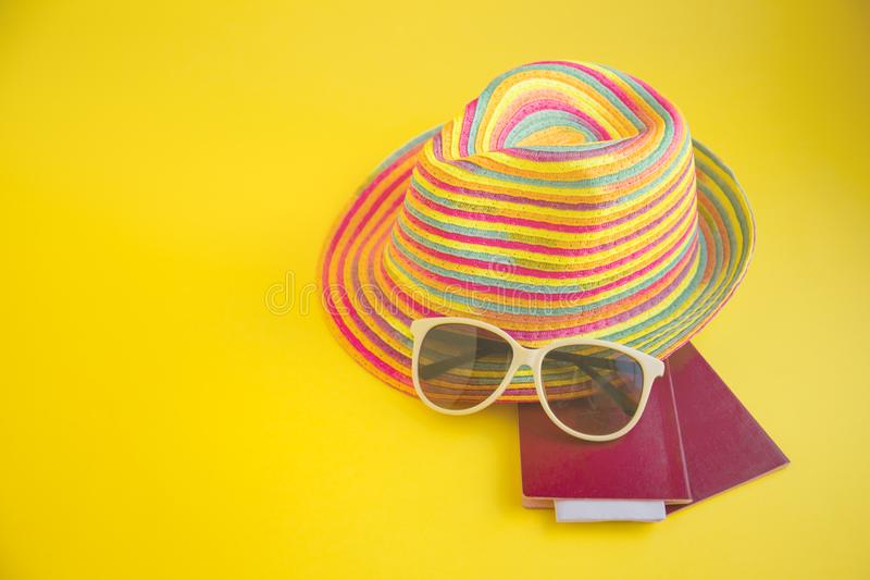 hat , sunglasses , passport on a yellow background Top view essential travel items. Summer holiday background. Travel planning. A royalty free stock photos