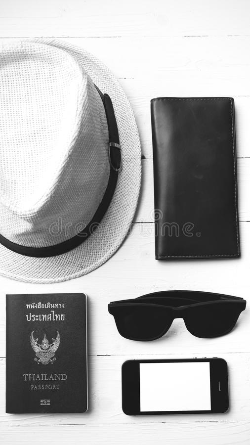 Hat sunglasses smart phone and passport black and white color. Hat sunglasses smart phone and passport over white table black and white color stock images
