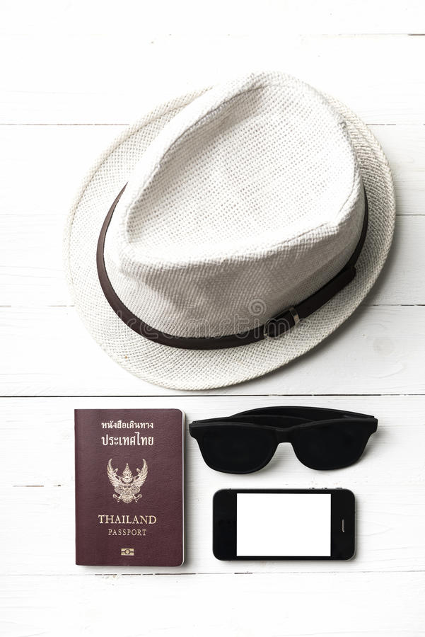 Hat sunglasses smart phone and passport. Over white table royalty free stock photo