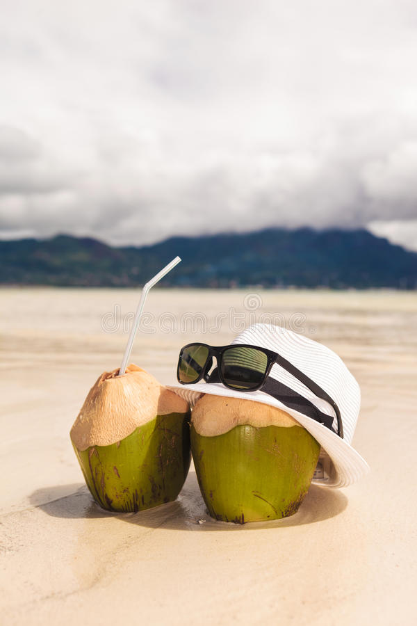 Hat and sunglasses with two coco nut cocktails on beach stock photography