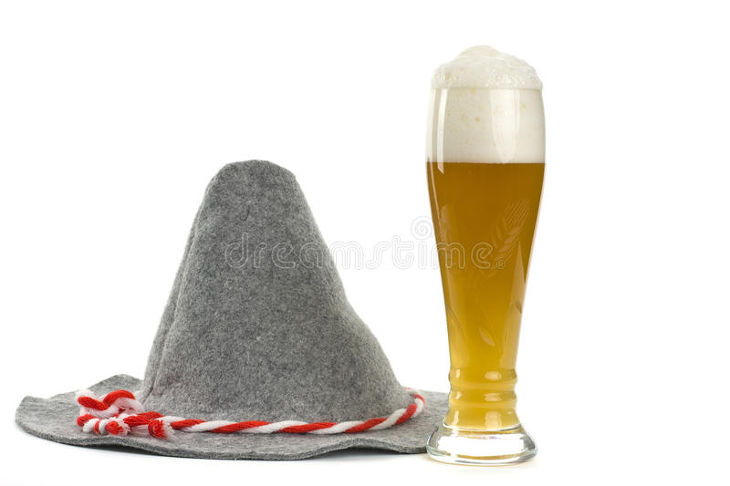 Hat and wheat beer. A hat and a glass of wheat beer on a white background shown royalty free stock photo