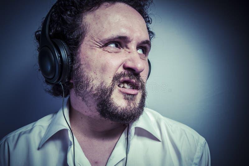 Hata musik, mannen med intensivt uttryck, den vita skjortan royaltyfri foto