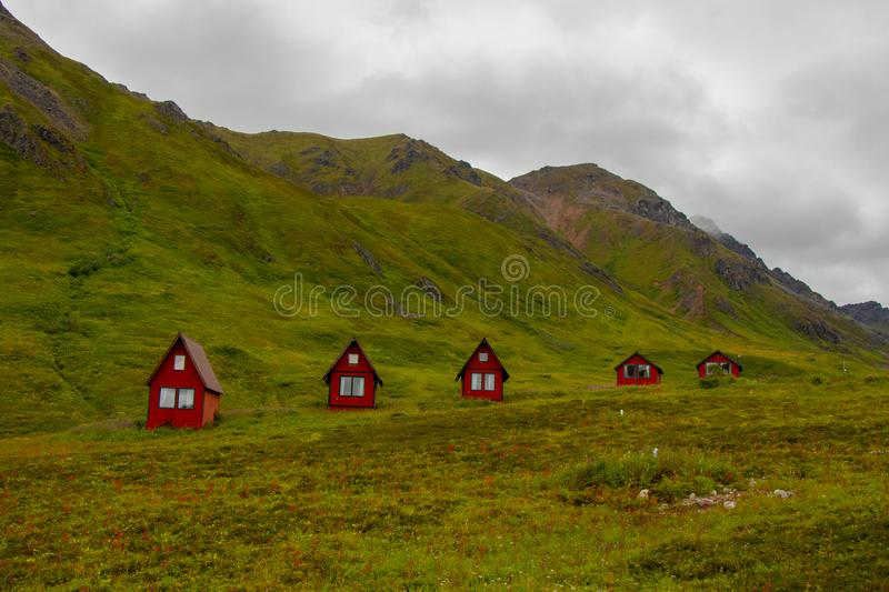 Abandoned red cabins sit in the green lush mountains of Alaska s Hatcher Pass near Independence Mine, United States of America. The Hatcher Pass Lodge is a royalty free stock photography