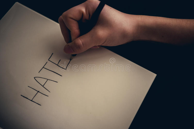 Hate concept - hand writing hate on book royalty free stock photography