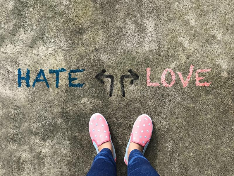 Hate or Love arrow and pink slipper shoe on concrete background. Hate or Love arrow and pink pastel slipper shoe on concrete background royalty free stock image