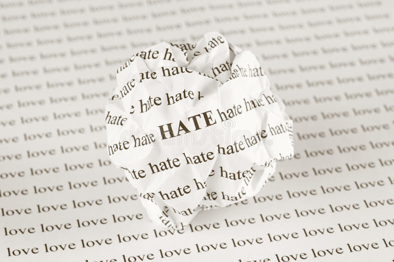 Hate or love. Crumpled paper ball with words Hate on background with words Love. Sepia royalty free stock image