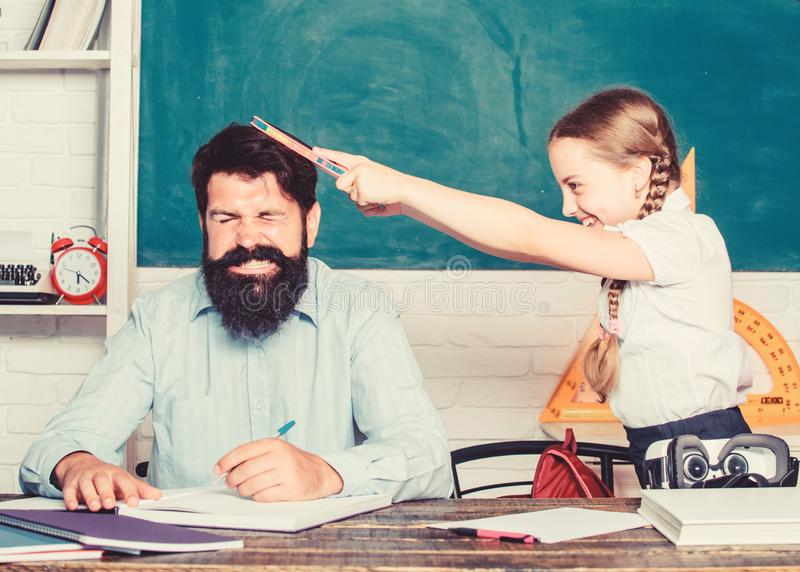 Hate school. private lesson. back to school. Private teaching. small girl child with bearded teacher man in classroom. Hate school. private lesson. back to royalty free stock photos