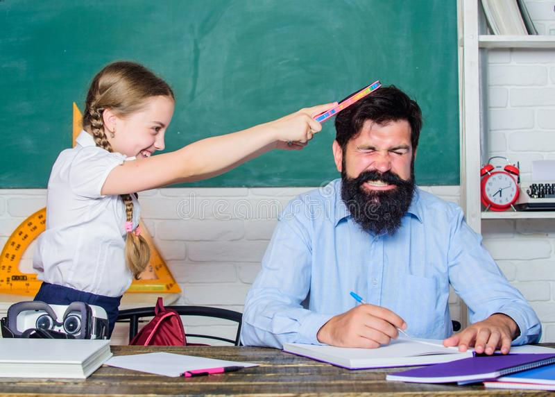 Hate school. private lesson. back to school. Private teaching. small girl child with bearded teacher man in classroom. Hate school. private lesson. back to stock photo