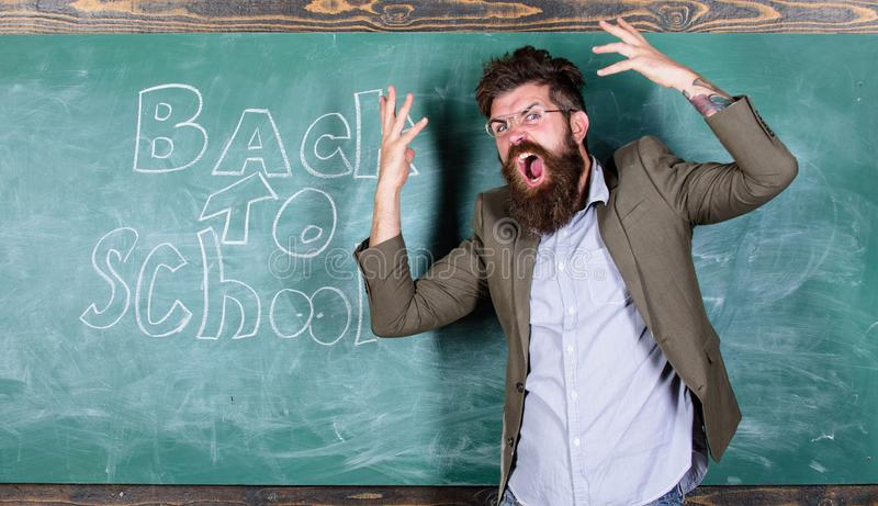Hate school. Teacher goes mad about schooling. Teacher or educator stands near chalkboard with inscription back to. School. Teacher unhappy shouting stock image