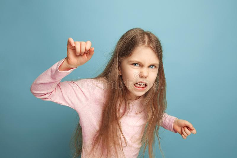The hate. Teen girl on a blue background. Facial expressions and people emotions concept. The hate, rage. The screaming surprised teen girl on a blue studio stock image