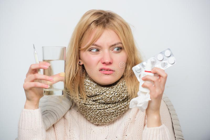 Hate to be ill. Ill woman treating symptoms caused by cold or flu. Cute sick girl taking anti cold pills. Unhealthy. Woman holding pills and water glass stock images