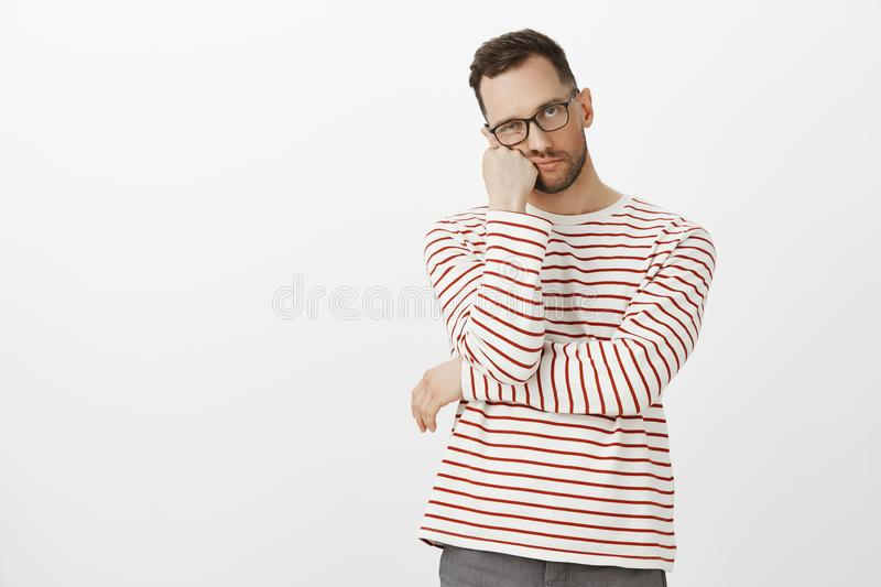Hate waiting in queues. Portrait of annoyed tired handsome guy with bristle in black eyewear, leaning face on hand and. Looking indifferent at camera, standing stock images