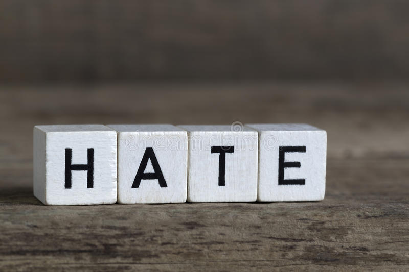 Hate, written in cubes. On a wooden background royalty free stock photo