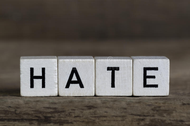Hate, written in cubes. On a wooden background royalty free stock photography