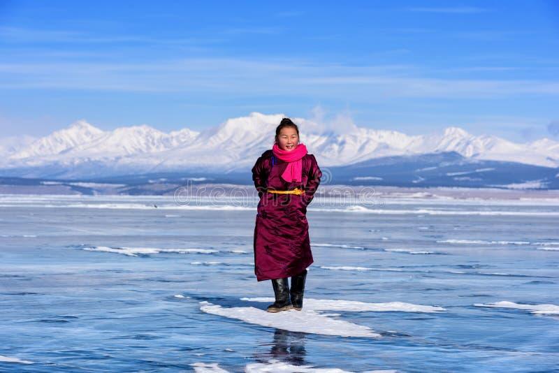 Hatgal, Mongolië, Febrary 23, 2018: het Mongoolse meisje draagt in traditionele kleren heeft pret op een bevroren meer Khuvsgul stock afbeelding