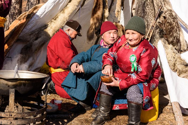 Hatgal, Mongolia, Febrary 25, 2018: older Mongolian lady and two men are sitting next to a stove near the yurt. In sunny day royalty free stock image