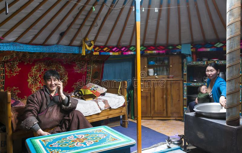Young mongolian nomad family in their home ger yurt. Hatgal, Mongolia, 3rd March 2018: mongolian family in their home ger, mother breastfeeding her baby stock image