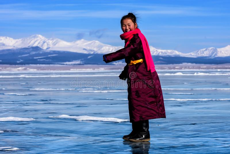 Hatgal, Mongolie, Febrary 23, 2018 : la fille mongole porte dans des vêtements traditionnels a l'amusement sur un lac congelé Khu photo libre de droits
