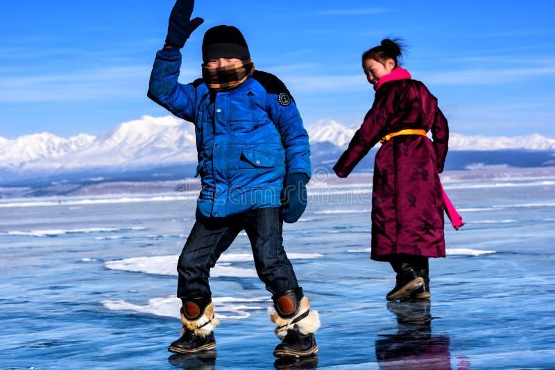 Hatgal Mongoliet, Febrary 23, 2018: den mongolian flickan och pojken bär i traditionell kläder har gyckel på en djupfryst sjö royaltyfri fotografi