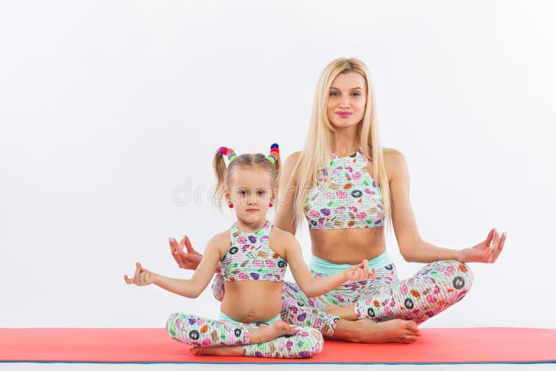 Hatha yogakondition Barnet fostrar och dotterövningen tillsammans inomhus Familjblick royaltyfri fotografi