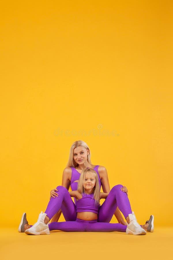 Hatha yogakondition Barnet fostrar och dotterövningen tillsammans inomhus Familjblick royaltyfria bilder