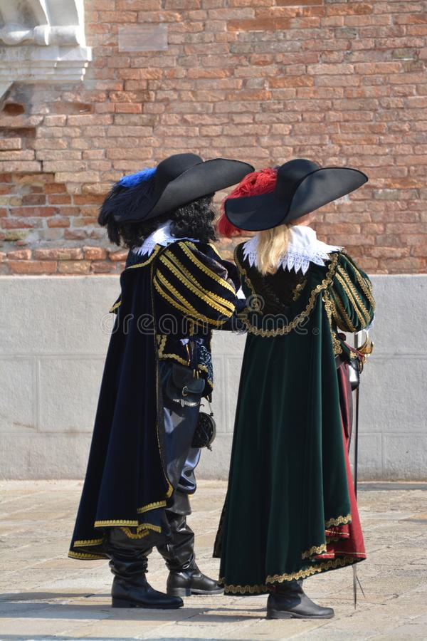 Two people dressed as 17th century at the Venice carnival. Hats with feathers, cloaks, boots, swords worn by two people disguised as soldiers of the 1600s ar the stock image