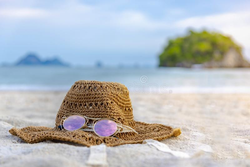 Hats and glasses are located on the beach, blue sea, during the day of relaxing or long holidays stock image