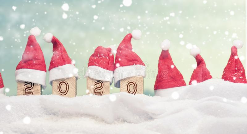 Hats of Santa with wooden blocks in snow. Many hats of Santa in a row with snow, Year 2020 on wooden blocks, New Year or Christmas background, panoramic view stock photography