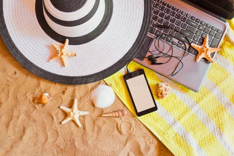 Hatt, bärbar dator och smartphone med sjöstjärnor och snäckskal på sandstranden royaltyfri foto