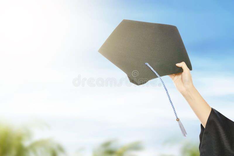 Hatt för handinnehavavläggande av examen med bakgrund för blå himmel arkivbild