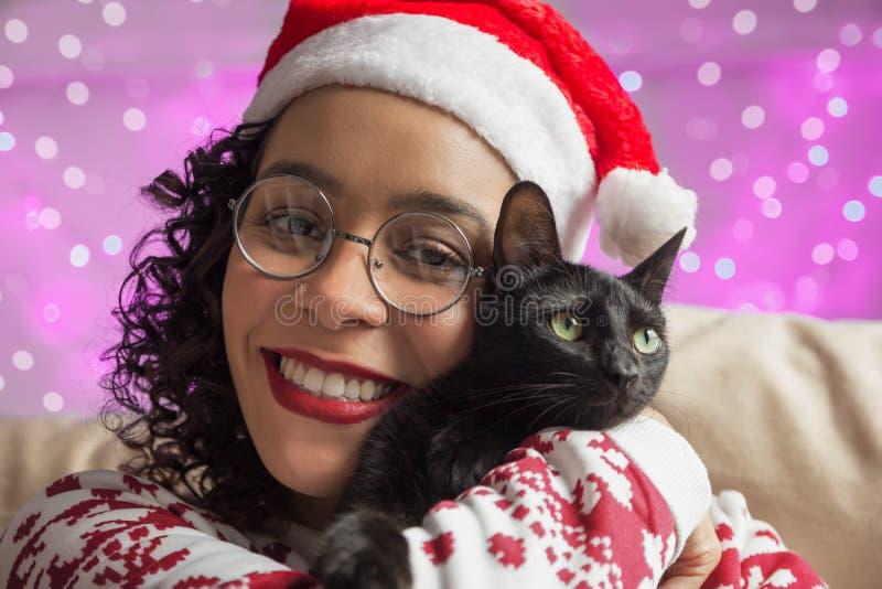 Hatt för jultomten för afrikansk amerikankvinna bärande och förtjusande husdjurkatt f fotografering för bildbyråer