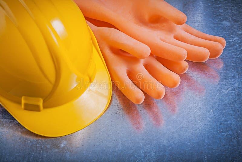 Hatt för rubber handskar för elektriker hård på utvald metallisk bakgrund arkivbild