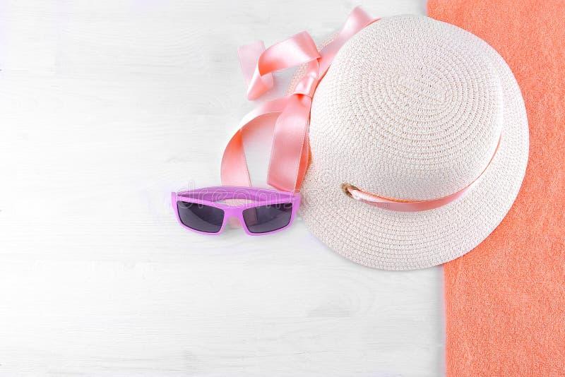 hatt med ett rosa band och rosa solglasögon på en orange handduk Vit träbakgrund, bästa sikt arkivfoto