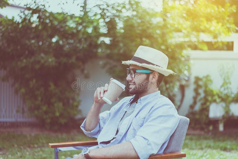 Hatt och exponeringsglas för Caucasian man som bärande dricker kaffe på utomhus-, lyckligt och ler, avslappnande tid arkivfoto