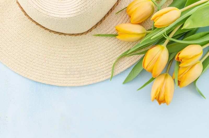 Hatt och gula tulpan över ljust - blå bakgrund Vårsommar dekorerade blomningen, kvinnaacessories, plan lekmanna- bästa sikt royaltyfria bilder
