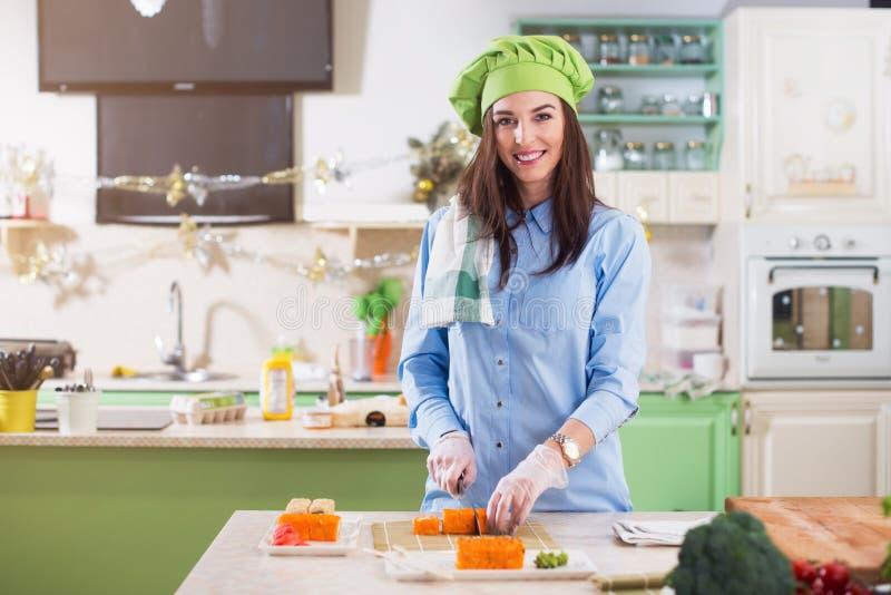 Hatt och handskar för kock s för kvinnlig kock som bärande gör japanska sushirullar, le som ser kameran i köket royaltyfri bild