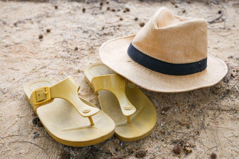 Hatt och skor på stranden arkivfoto