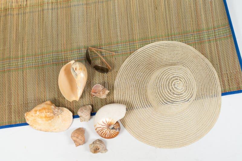 Hatten, solglasögon och skalen på en färgrik filt på isolerad vit bakgrund royaltyfri bild